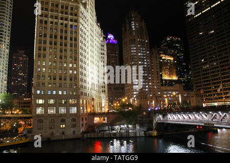 The Wrigley Building, Tribune Tower, and 401 N Michigan Ave along the Chicago River in downtown Chicago, Illinois at night - Stock Photo