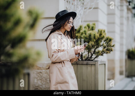 Young mixed woman use mobile phone and smiling in urban background. Young girl wearing casual clothes - Stock Photo
