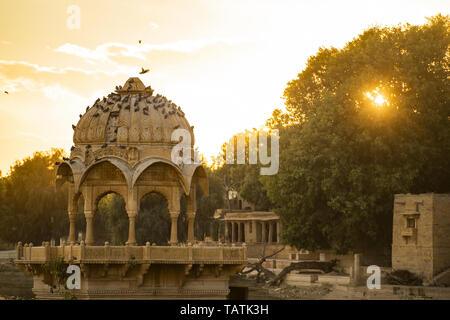 Spectacular view of the Gadi Sagar Lake (Gadisar) with an ancient temple during sunset. - Stock Photo