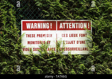 Bi-lingual English and French language surveillance warning sign with red lettering hung on chain link fence in green cedar hedge. - Stock Photo
