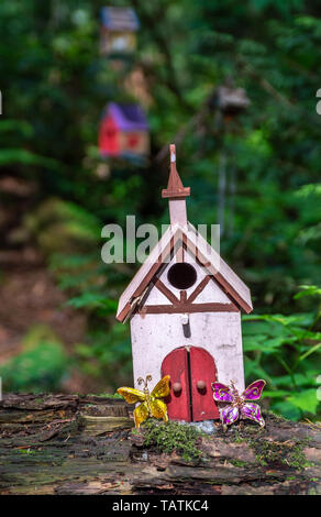 Tiny cute and colorful homemade fairy house in a whimsical style sitting on log in woodland forest. - Stock Photo