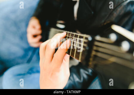 Detail of the fingers of a guitarist placed on the fret of the mast of the guitar playing a chord doing Tapping. - Stock Photo