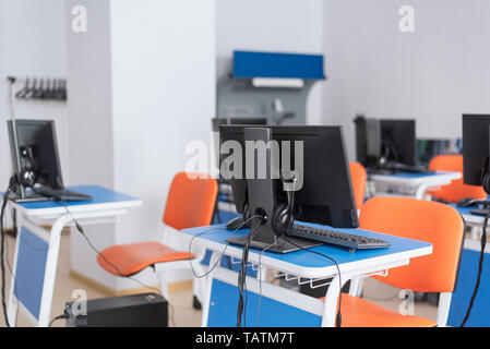 empty computer classroom with bright blue desks and orange chairs. teaching children programming. there is not anyone. - Stock Photo