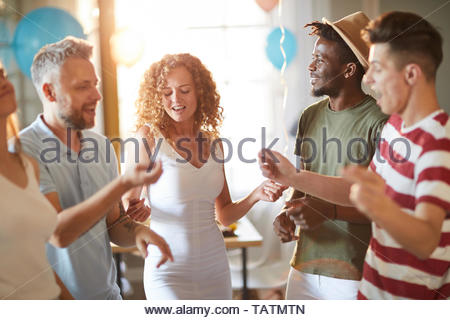 Multi-ethnic group of young people dancing during party lit by sunlight, copy space - Stock Photo