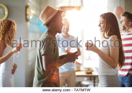 Side view at young multi-ethnic couple chatting during party and drinking wine, copy space - Stock Photo