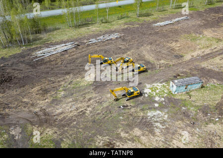 Aerial side view of four yellow crawler excavators standing on ground near the construction site and waiting for the working day to start digging the  - Stock Photo