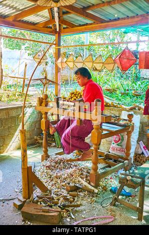 PINDAYA, MYANMAR - FEBRUARY 19, 2018:  The carpenter works on wood turning lathe in umbrella workshop, he makes bamboo handles for parasols, on Februa - Stock Photo