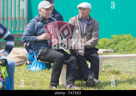RUSSIA, Nikolskoe village, Republic of Tatarstan 25-05-2019: A group of old men sitting on the bench. One of them playing accordion. Mid shot - Stock Photo