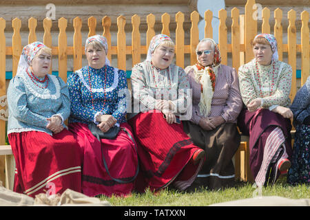 RUSSIA, Nikolskoe village, Republic of Tatarstan 25-05-2019: A group of old women sitting on the bench and talking. Mid shot - Stock Photo
