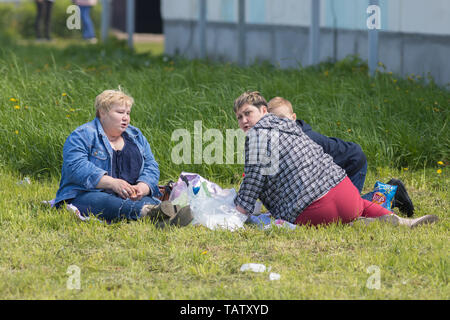 RUSSIA, Nikolskoe village, Republic of Tatarstan 25-05-2019: Three mature overweight women sitting on the blanket in a village and having a picnic. An - Stock Photo