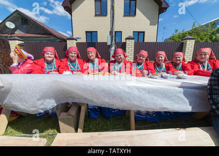 RUSSIA, Nikolskoe village, Republic of Tatarstan 25-05-2019: A group of old women sitting on the bench by the table. Mid shot - Stock Photo