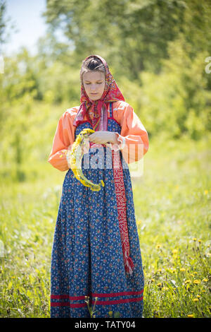 RUSSIA, Nikolskoe village, Republic of Tatarstan 25-05-2019: A young woman in traditional russian clothes making a wreath. Mid shot - Stock Photo