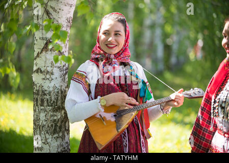 Young woman in traditional russian clothes standing in the forest and holding balalaika, midle shot - Stock Photo