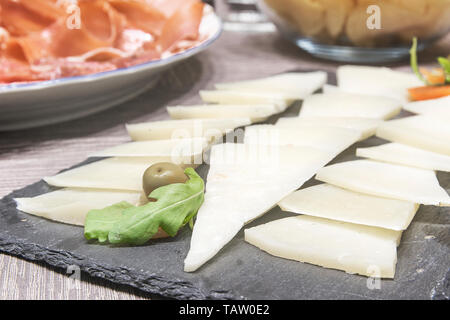 Hard cheese next some iberian ham ready for typical Spanish tapeo. Travel and cousin concept with empty copy space for Editor's text. - Stock Photo