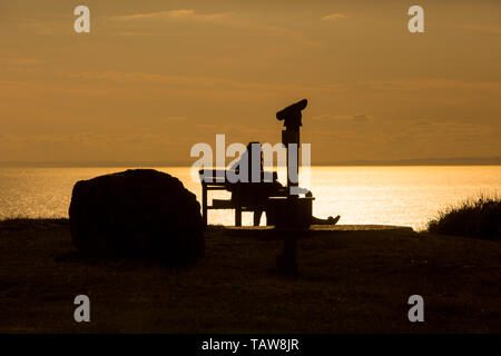 Portland, Dorset, UK. 28th May, 2019. A man and woman are silhouetted against the low sun on the sea as they enjoy the warm late afternoon on the Isle of Portland, Dorset. Peter Lopeman/Alamy Live News - Stock Photo