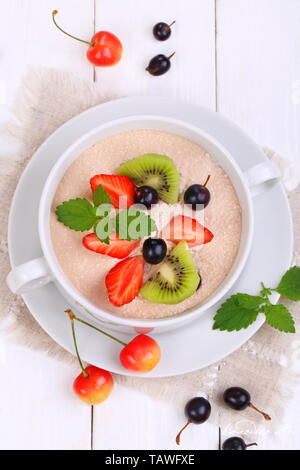 Oatmeal with strawberries, black currant, mint on a white wooden background - Stock Photo
