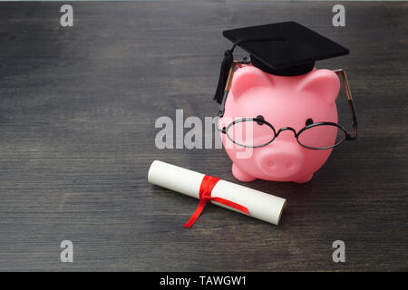 Piggy bank with a grad cap and diploma on wooden table, Education scholarship - Stock Photo