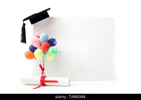 Black Graduation cap on blank white billboard, diploma and balloons - Stock Photo