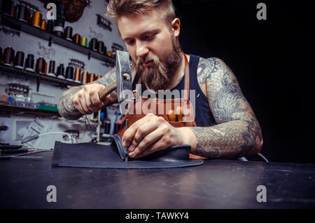 Leather Currier cutting out leather goods . - Stock Photo
