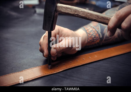 Leather workman manufacturing new leather product in leather shop. - Stock Photo