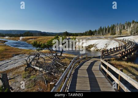 A walkway, bridge with wooden rails across Yellowstone river - Stock Photo