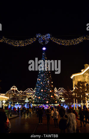 Christmas tree and lights in Main Street, Disneyland Paris, France. Eurodisney. People looking at decorations at night. Illuminations - Stock Photo