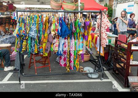 Colourful dresses on sale at Totnes Market, Totnes, Devon, UK - Stock Photo