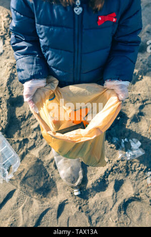 Girl showing garbage collected from the beach - Stock Photo