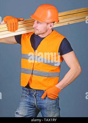 Hardy labourer concept. Carpenter, woodworker, labourer, builder on busy face carries wooden beams on shoulder. Man in helmet, hard hat and protective gloves holds wooden beam, grey background. - Stock Photo
