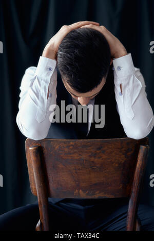 Tired and bored handsome man holding head by hands. Crisis, depression concept - Stock Photo