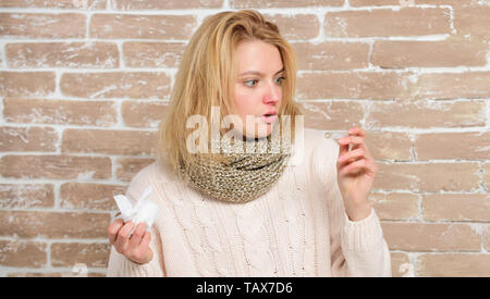 High temperature. Sick woman holding fever thermometer. Cute ill girl measuring body temperature. Unhealthy pretty woman suffering from fever heat. Becoming unwell with cold or flu. - Stock Photo