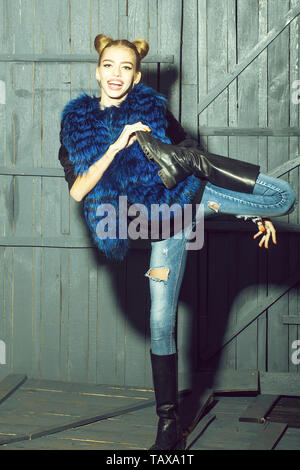 Full length view of one straight slender funny young smiling happy woman with cool hairstyle in torn jeans and waist coat of blue fur with flexible bo - Stock Photo
