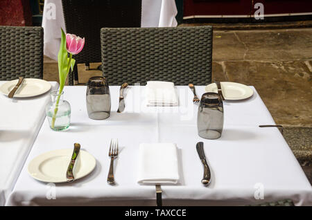 A table at a restaurant neatly laid out with place settings ready customers. - Stock Photo