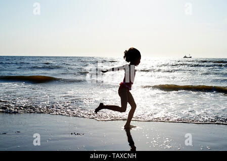 Silhouette of two young girls having fun playing, running  and splashing in the ocean at the beach in summer sunshine during sunset - Stock Photo