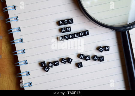 Ask an Expert on wooden block and magnifying glass. Motivation concept - Stock Photo