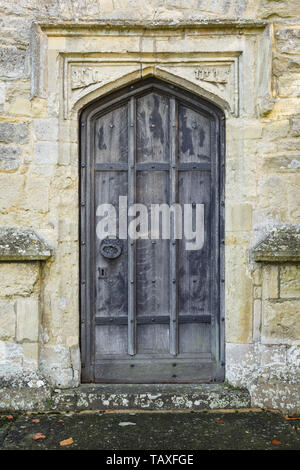 Ancient arched wooden door in entrance to an old medieval stone church in England - Stock Photo