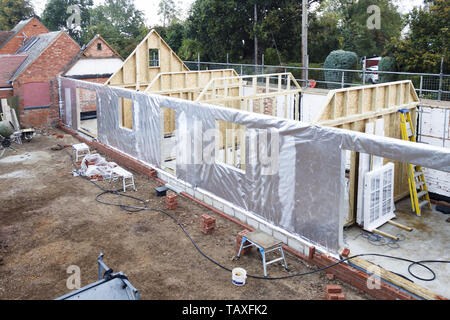 Timber frame house under construction with foil thermal insulation - Stock Photo