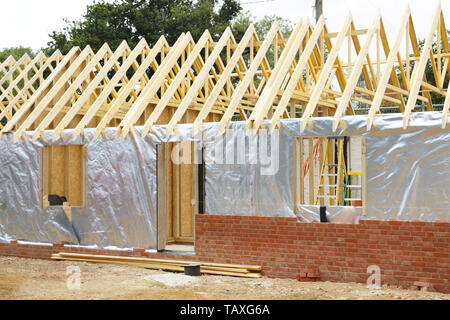 Timber frame house extension or annexe under construction with modern foil insulation and exterior brick wall - Stock Photo