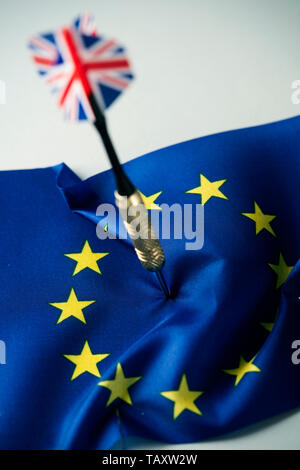 closeup of a dart patterned with the flag of the United Kingdom stuck in the middle of a flag of the European Union - Stock Photo