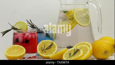 Cold drink with lemon, ice cubes and black currant in a jar glass. Refreshing soda lemonade cocktail. Mineral tonic fizzy water with bubbles. White background - Stock Photo