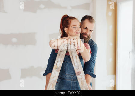 Loving young couple doing DIY home improvements renovating their house standing in an affectionate embrace with the woman leaning on a ladder on site - Stock Photo
