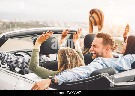 Group of friends having fun in convertible car during road trip at sunset - Young travel people driving a cabriolet during summer holidays - Stock Photo