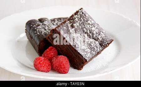 Extremely rich fudgy chocolate brownies made without any grains, totally gluten free. with raspberries. - Stock Photo