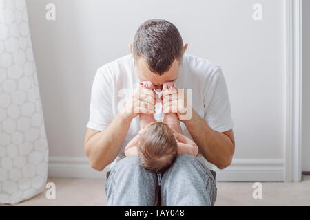 Caucasian father holding newborn baby on laps knees. Male man parent playing with child daughter son feet heels. Authentic lifestyle documenatry funny - Stock Photo