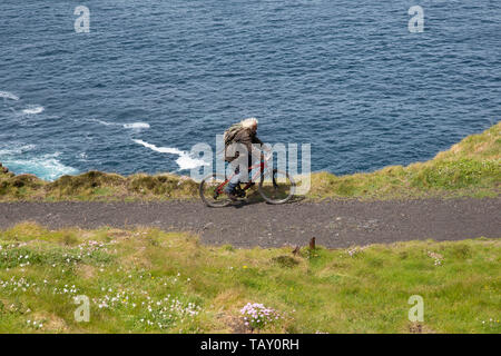 Long haired male cyclist riding along the North Coastal gravel path in Cornwall close to the steep cliff drop to the Atlantic ocean - Stock Photo