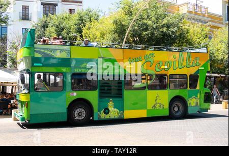 A Tour Por Sevilla tour bus passing the Alameda de Hercules in Seville - Stock Photo