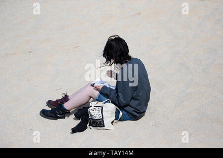 Young artist girl sitting on a white sandy beach sketching in the summer sunshine. - Stock Photo