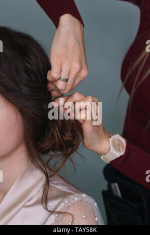 Hairdresser at work in process of creating wedding hairstyle. Master fixes lower topknot of hair with invisible hairpins and hat pins. Beauty is in de - Stock Photo