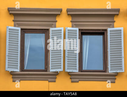 Photograph of two weatered, wood blue window shutters from the medieval town of Flornce, Italy in the heart of Tuscany. - Stock Photo