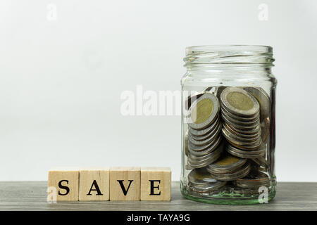 Saving money concepts. Stacked coins in glass jar and wooden block on wood table with white background.